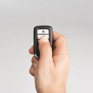 Hand pressing a remote fob